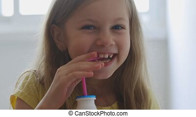 Little girl with blue eyes is drinking milk. child drinks milk from a small bottle through a pink tubule indoors lifestyle morning breakfast