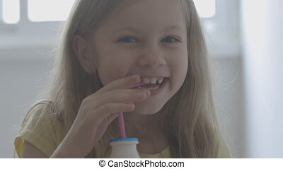 Little girl is drinking milk. child drinks milk from a small bottle through a pink tubule indoors lifestyle morning breakfast