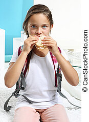 girl is eating a sandwich