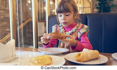 Little girl is eating a sweet roll