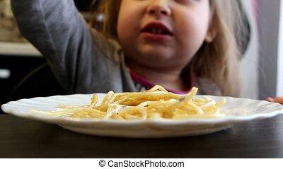 Little girl is eating spaghetti