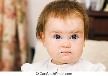 Cute little girl is frowning, face portrait