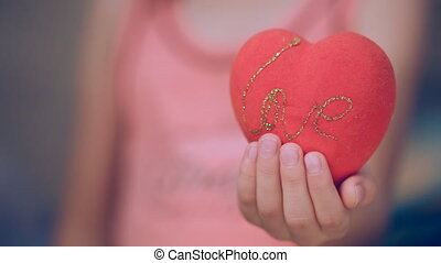 Little girl is holding a heart