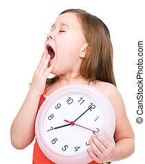 Little girl is holding big clock