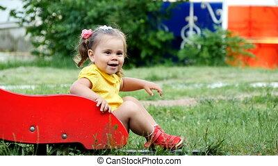 Little girl is laughing sitting on a children's slide