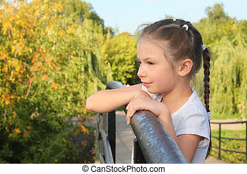 little girl is lean elbow on bridge fence and looking...