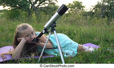 little girl is looking through a telescope