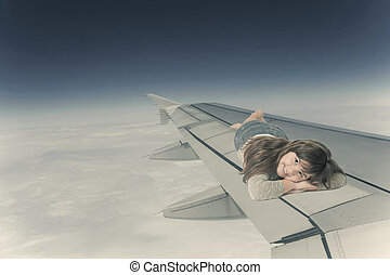 Little girl is lying on the wing of an aircraft