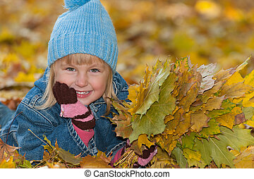 Little girl is lying on the yellow leaves
