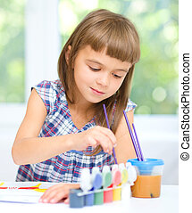 Little girl is painting with gouache