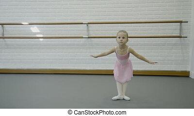 Little girl is performing dancing movements in ballet school.