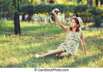little girl is played by photo camera sitting on grass in park. Doing Selfie and photographing the world around