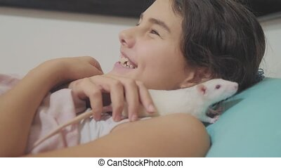 little girl is played on a bed with a white homemade handmade rat mouse. funny video rat crawling over a little girl. lifestyle girl and white mouse pet concept