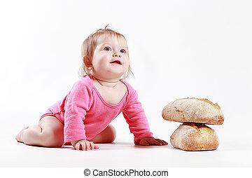 little girl is played with bread in the studio on a white background
