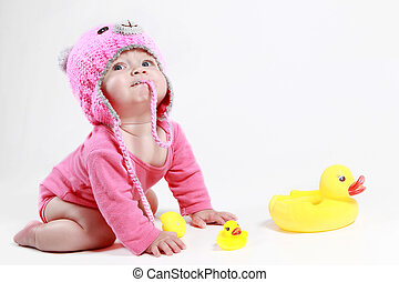 little girl is played with ducklings in the studio on a white background