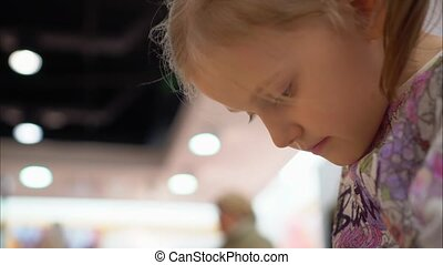 Little girl is playing a game using a smartphone. Face close-up