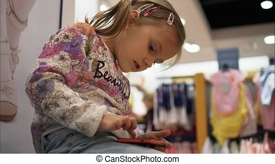 Little girl is playing a game using a smartphone in the store