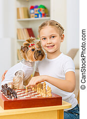 Little girl is playing chess with her dog.