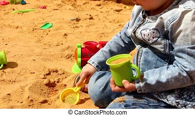 Little girl is playing in the sandbox