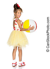 Little girl is playing with a ball