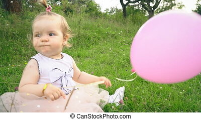 little girl is playing with a balloon in the nature