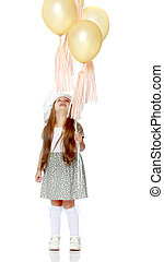 Little girl is playing with a balloon