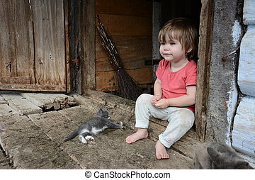 little girl is playing with a gray cat