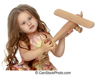 Little girl is playing with a plane
