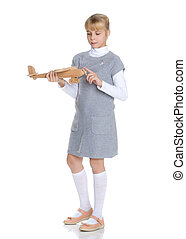 Little girl is playing with a wooden plane.