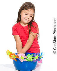 Little girl is playing with flowers, isolated over white