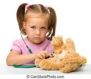 Little girl is playing with her teddy bear