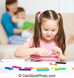Little girl is playing with plasticine