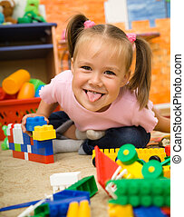 Little girl is playing with toys in preschool - Little girl...