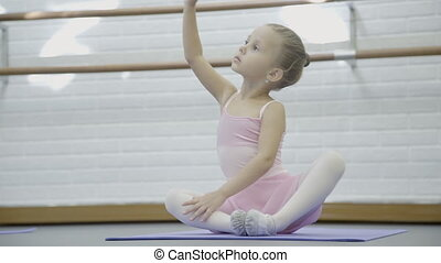 Little girl is practicing in ballet school indoor. Child...