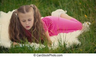 little girl is reading a book - little girl reads a book...