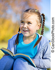 Little girl is reading a book outdoors