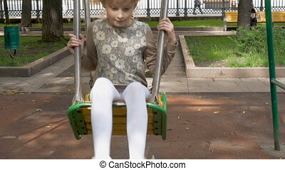Little girl is riding on a swing.