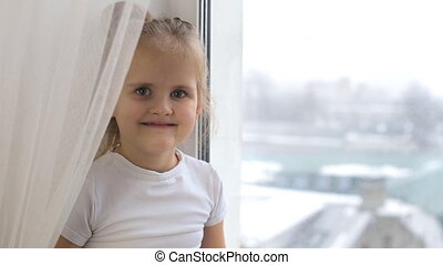 Little girl is sitting by the window and looking at the camera with a smile