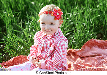 Little girl is sitting on a blanket in the summer field