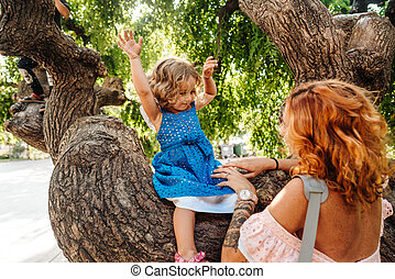 little girl is sitting on a branch