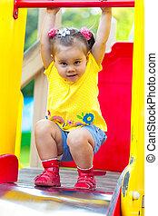 Little girl is sitting on a children's slide