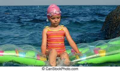 Little Girl Is Sitting On A Mattress In The Sea