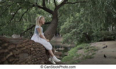 Little girl is sitting on a tree