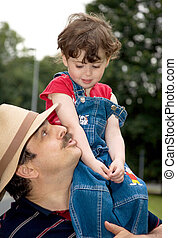 little girl is sitting on daddy's shoulder