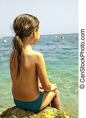 Little girl is sitting on the beach