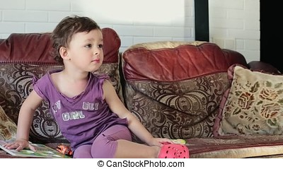 Little girl is sitting on the couch.