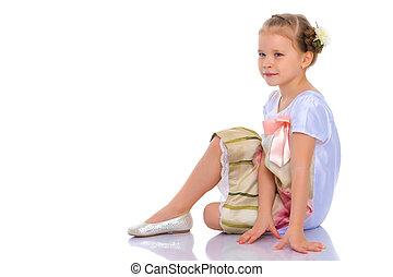 Little girl is sitting on the floor.