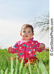 little girl is sitting on the grass