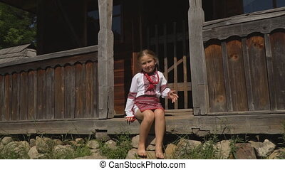 little girl is sitting on the porch of the house - Little...