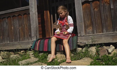 little girl is sitting on the porch of the house